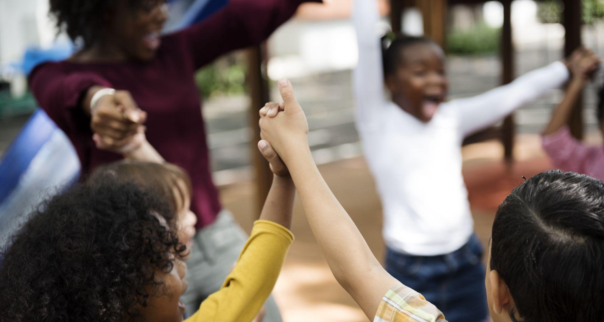 Group of diverse kindergarten students hands up together